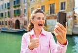 Closeup on happy young woman showing thumbs up and making selfie