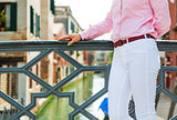 Closeup on happy young woman standing on bridge in venice, italy