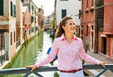 Smiling young woman standing on bridge in venice, italy