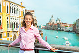 Smiling young woman standing on bridge with grand canal view in