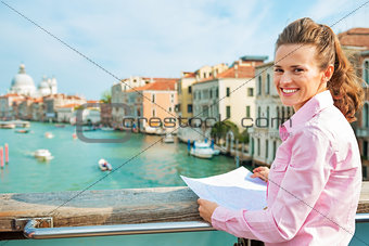 Portrait of happy young woman with map standing on bridge with g