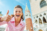 Happy young woman against campanile di san marco showing thumbs