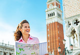 Portrait of smiling young woman looking at map against campanile