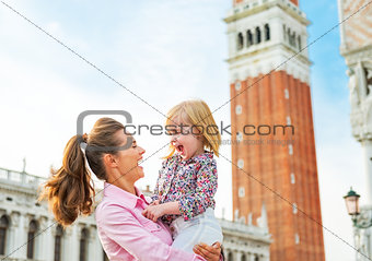 Portrait of smiling mother and baby against campanile di san mar