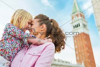 Portrait of mother and baby hugging against campanile di san mar
