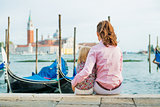 Portrait of mother and baby sitting on grand canal embankment in