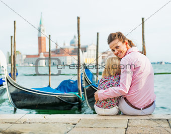 Portrait of happy mother and baby sitting on grand canal embankm