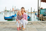 Portrait of smiling mother and baby on grand canal embankment in