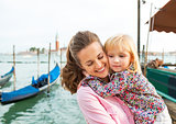 Portrait of happy mother and baby hugging on grand canal embankm