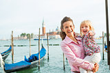 Portrait of happy mother and baby on grand canal embankment in v