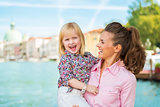Portrait of happy mother and baby standing on grand canal embank