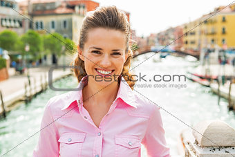Portrait of smiling young woman standing on bridge in venice, it