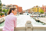 Happy young woman standing on bridge in venice, italy and lookin