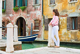Young woman standing on street in venice, italy and looking into