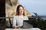 Happy woman working with her laptop in an hotel terrace