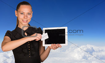 Beautiful businesswoman holding tablet PC and business card in front of screen. Blue sky with cloud layer as backdrop