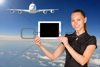 Beautiful businesswoman holding tablet PC. Blue sky, clowds and jet airliner as backdrop