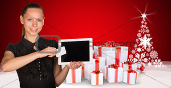 Beautiful businesswoman holding tablet PC. New Year tree and gifts as backdrop