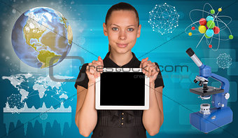 Beautiful businesswoman holding tablet PC.  Atom model and microscope beside. Globe, world map with geometric forms as backdrop