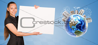 Beautiful businesswoman holding blank paper sheet. Beside is miniature Earth with houses on it