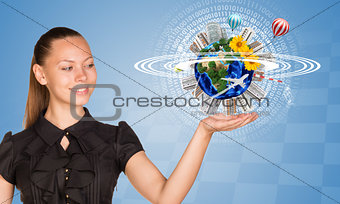 Beautiful businesswoman holding miniature Earth with trees, houses etc. on it