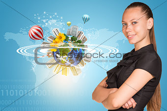 Beautiful businesswoman smiling and looking at camera.  Beside is miniature Earth with trees, houses etc.