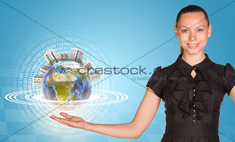 Beautiful businesswoman holding miniature Earth with houses on it.