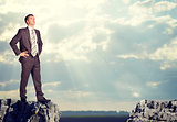 Businessman standing on the edge of rock gap