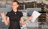 Beautiful woman holding blank paper sheet and felt pen ready to use. Construction site as backdrop