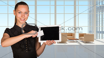 Beautiful businesswoman holding tablet PC. White roomy hall with sofas and coffee table as backdrop