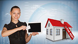 Beautiful businesswoman holding tablet PC.  Beside is house with tag for rent