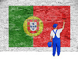 house painter covers brick wall with flag of Portugal