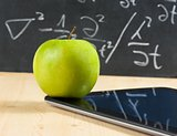 digital tablet pc and green apple in front of blackboard on wood table