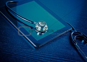 medical stethoscope on modern digital tablet in laboratory on wood table