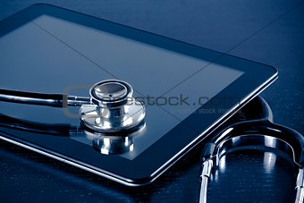 medical stethoscope on modern digital tablet pc in laboratory on wood table