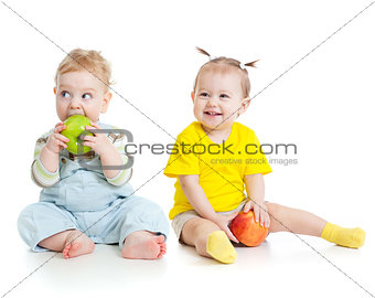 Baby boy and girl eating apples isolated