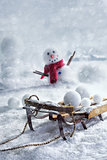 Wooden sleigh and snowballs with snowman