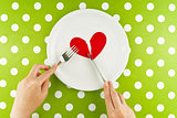 Woman eating broken heart on a white plate
