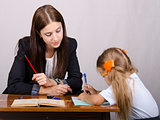 teacher teaches lessons with student sitting at table