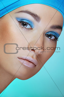 Close-up  portrait of attractive woman in turquoise scarf on the head with bright blue makeup