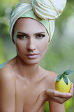 beautiful woman in yellow scarf on her head with lemon in hand over nature background