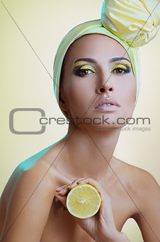 beautiful woman with festive makeup in yellow scarf on the head with lemon in hand