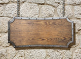 wood sign with metal frame on old stone wall