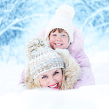Happy mother and kid lying in snowdrift outdoor