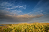 Lighthouse in landscape under dramatic stormy sky sunset in Summ