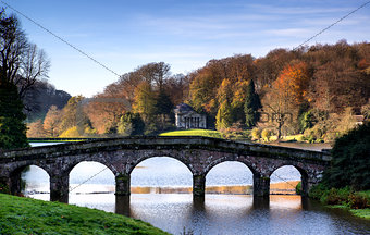 Bridge over main lake in Stourhead Gardens during Autumn.