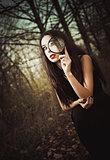 Strange goth girl looks through loupe