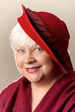 Close-up of white-haired woman in red hat