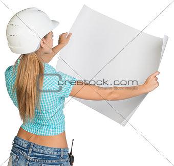 Beautiful woman builder holding in front of him large paper sheet. Rear view