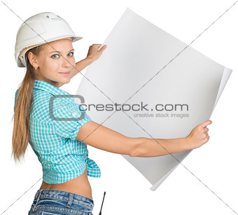 Beautiful woman builder looking at camera and holding in front of him large paper sheet. Rear view